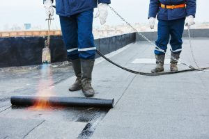 Wrokers using torch to seal flat roof