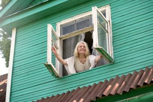 Lady leaning out a window, improving indoor air quality