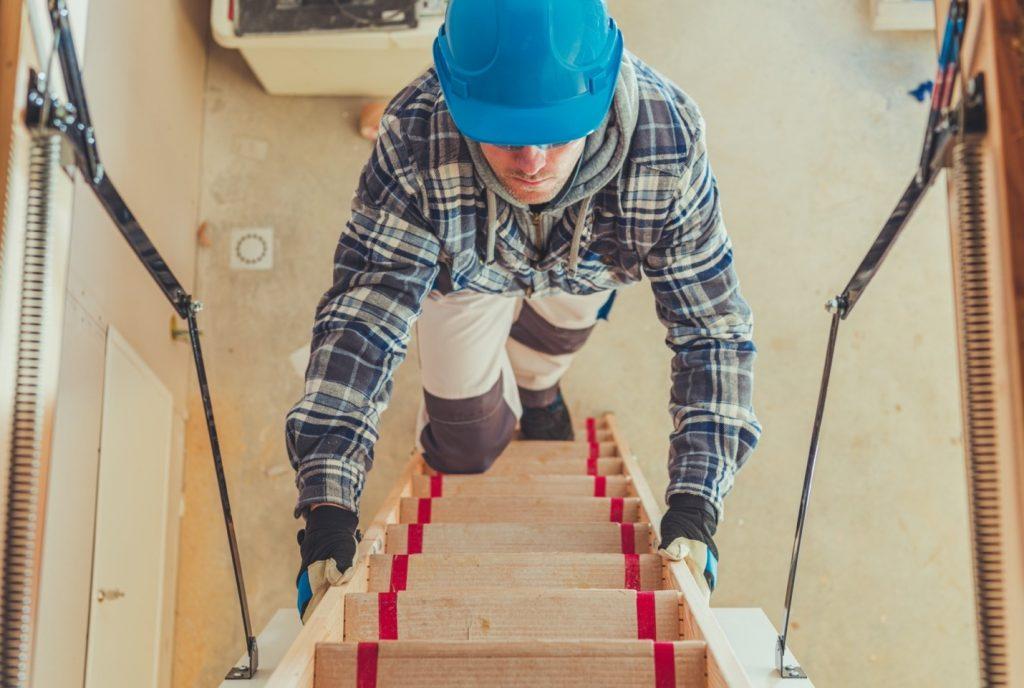 Man climbing stairs to attic